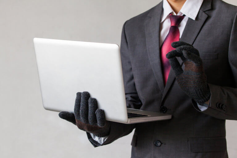 Business man wearing gloves and using computer
