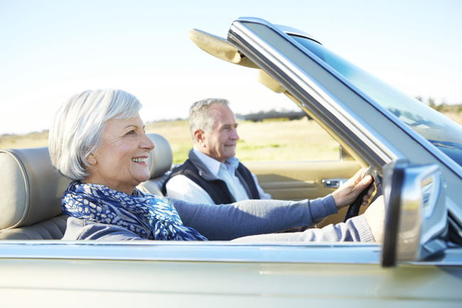 Happy couple driving through the countryside in a convertible